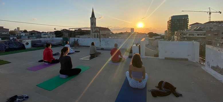 שיעורי יוגה על גג קסום ביפו בשקיעה בימי ראשון